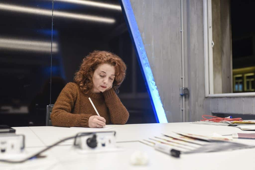 A woman takes notes in an public office space