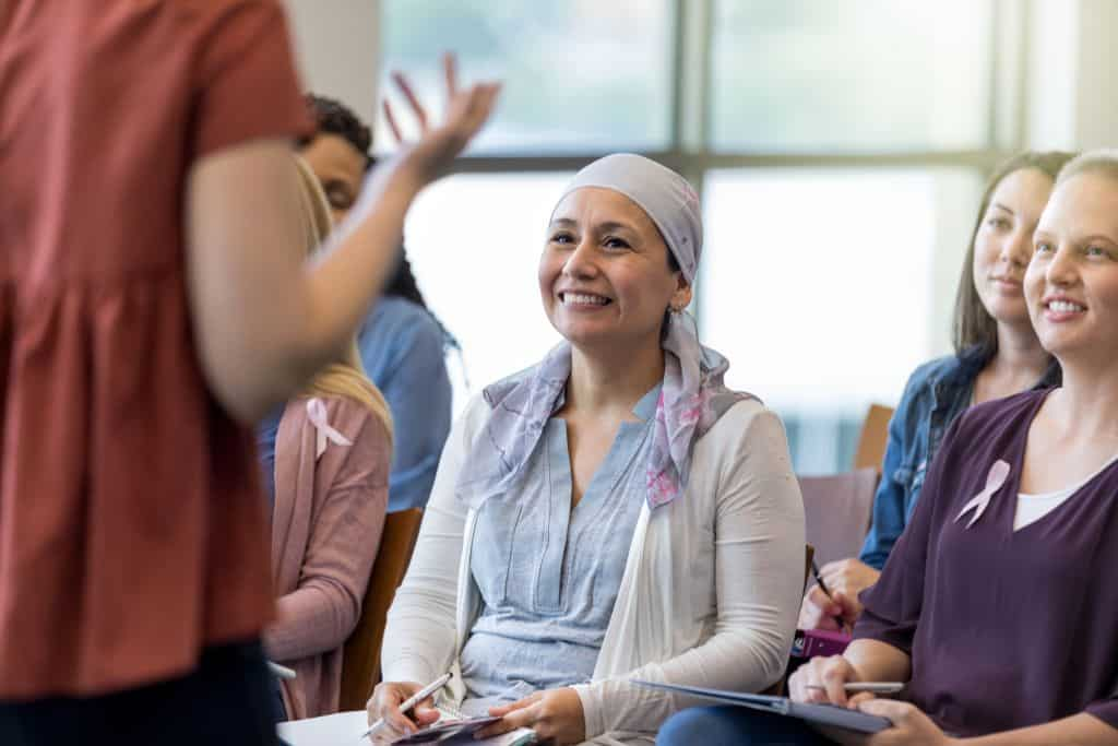 Unrecognizable conference speaker encourages women during cancer awareness event
