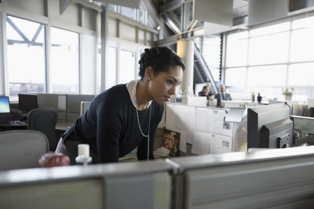 Businesswoman using computer in office cubicle