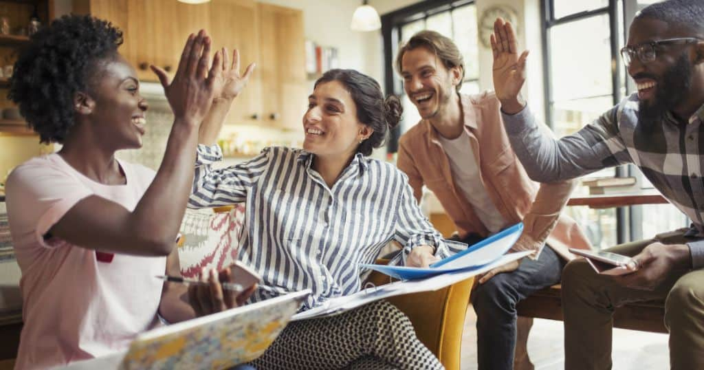 Creative business people high fiving in meeting