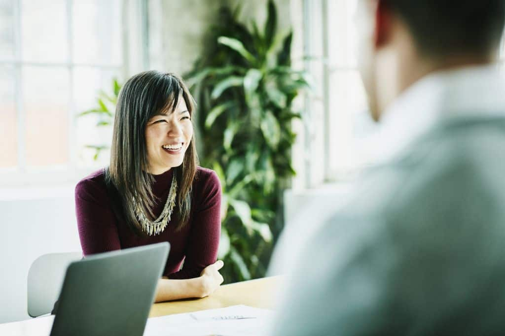 Smiling businesswoman leading project meeting in office conference room