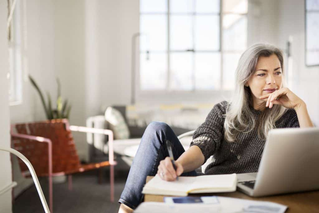 Mature woman writing in diary while working at home