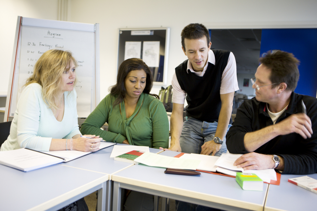 adult education: mature students debating a project with their teacher