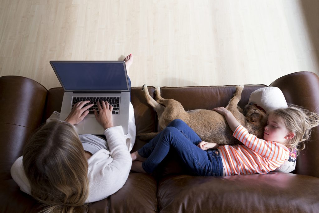 woman using laptop while daughter and dog sleep