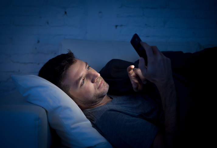 man in couch using mobile phone neetworking late night