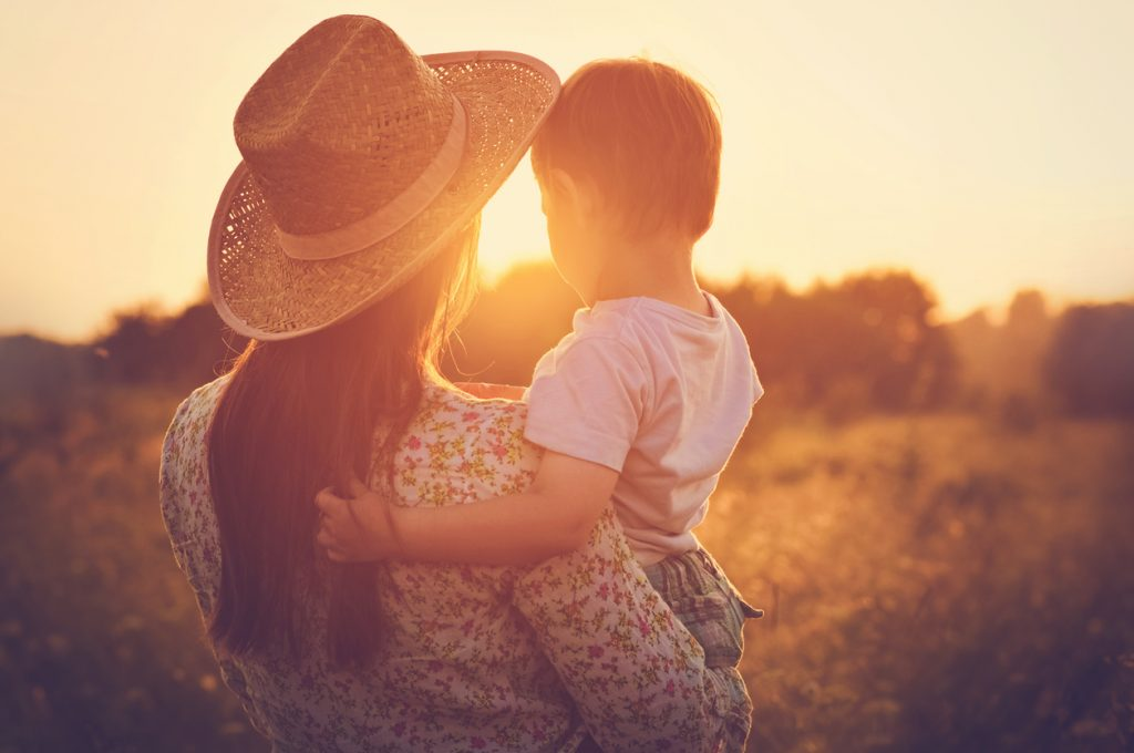 Mother and a baby enjoying beautiful sunset