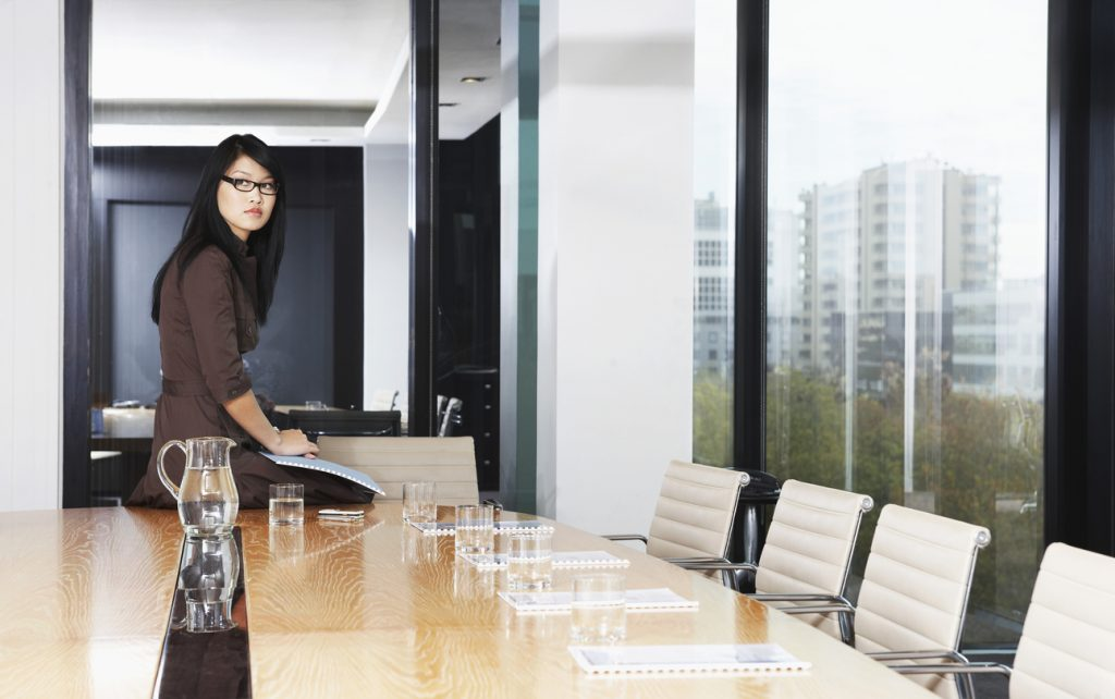 Businesswoman Sitting On Table In Boardroom
