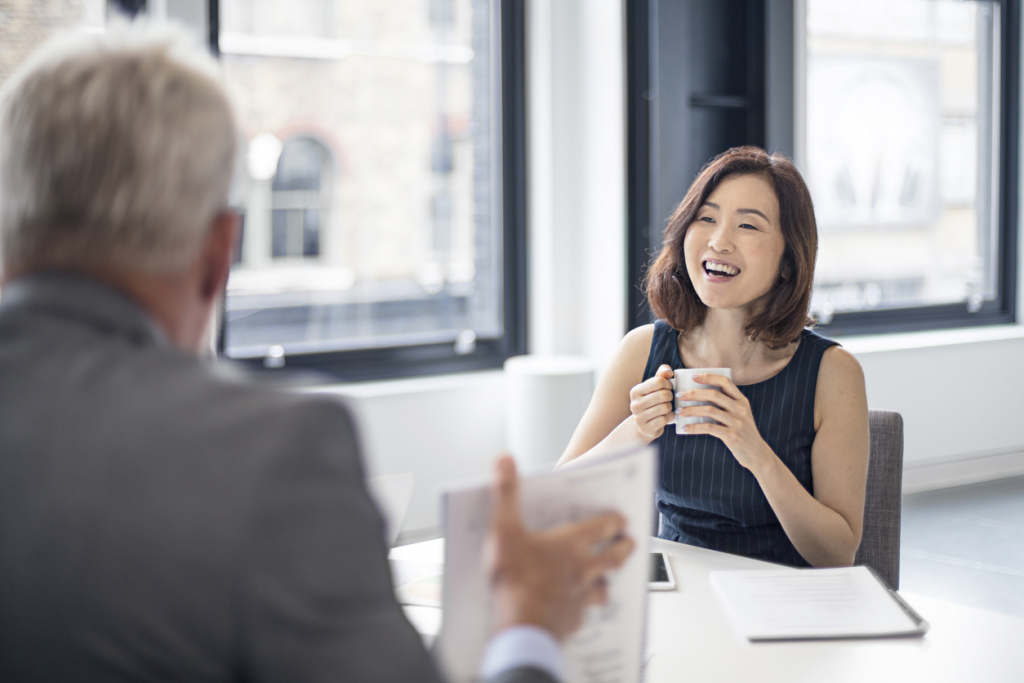 Happy businesswoman with mug looking at colleague