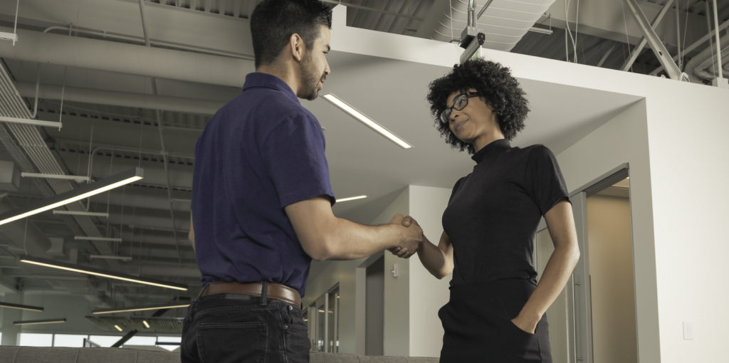 Two co workers meeting and shaking hands