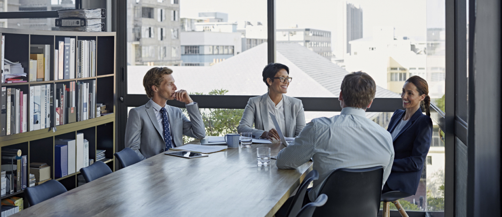 Businesswomen sitting with male colleagues at conference table