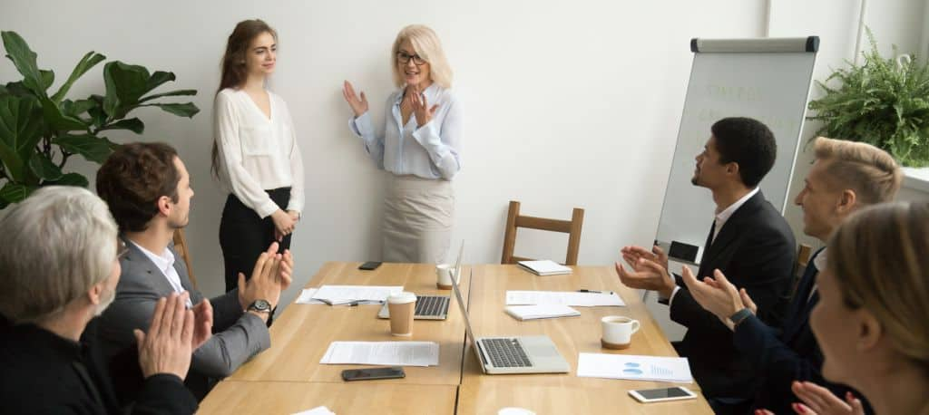 Senior woman boss introducing new worker, team welcoming at meeting