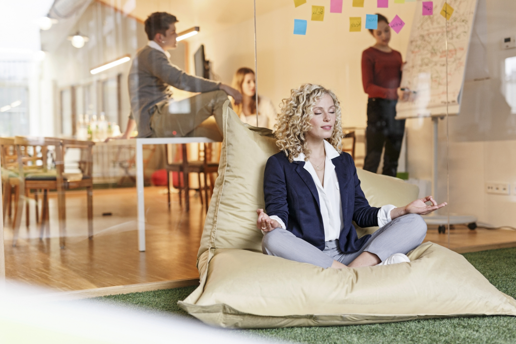 Woman doing yoga in bean bag with meeting in background