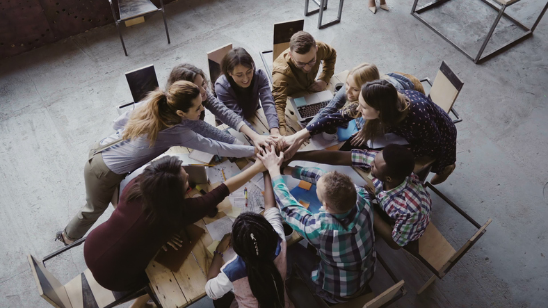 Top view of business team working at trendy loft office. Young mixed race group of people puts palm together on centre