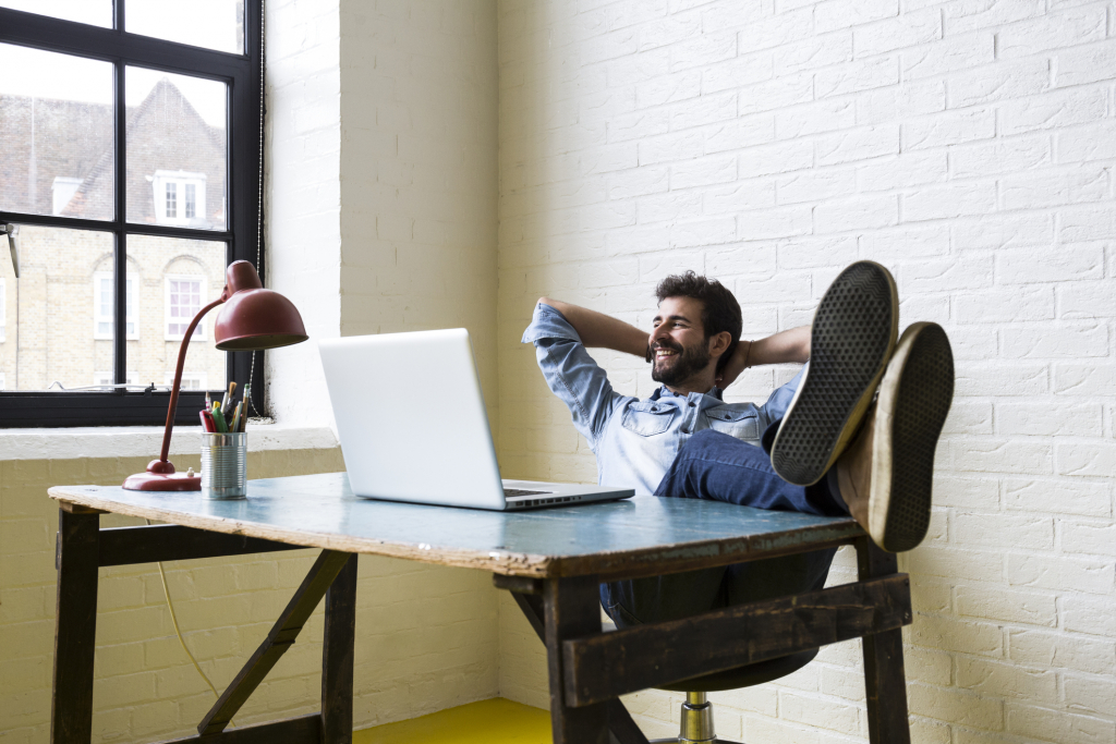 Smiling man sitting with feet up at desk looking out of window