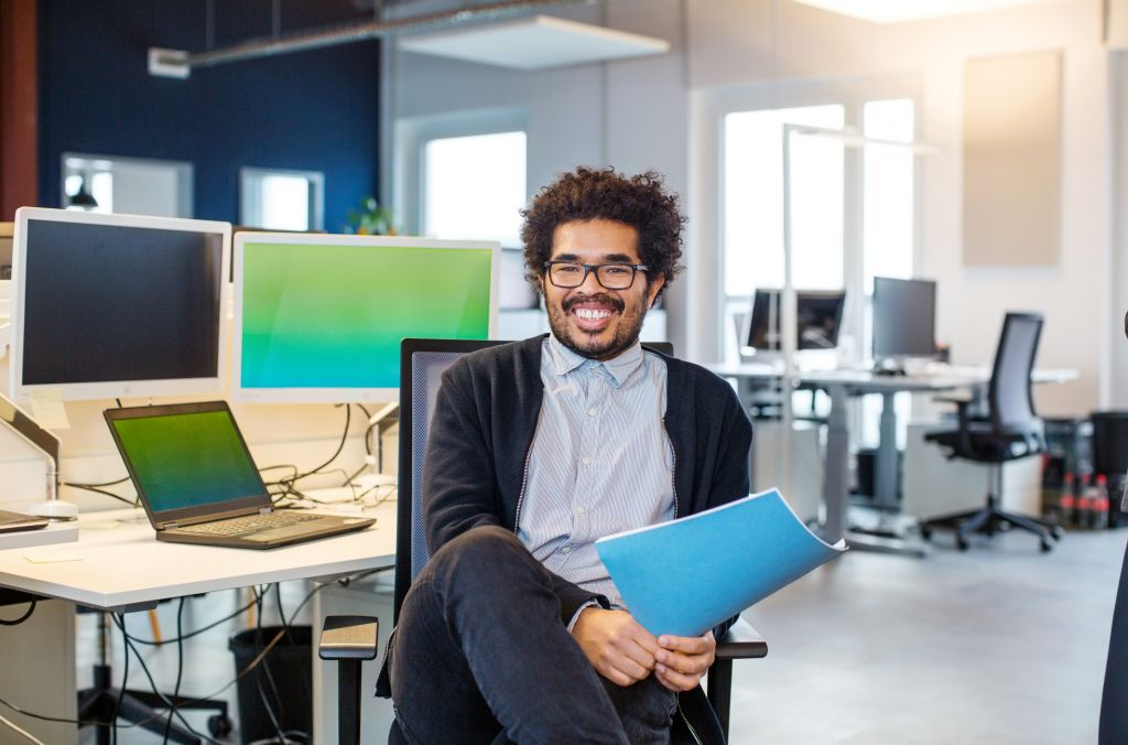 Happy young businessman sitting at his desk
