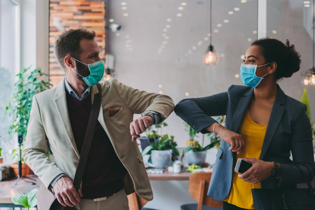 Business people greeting during COVID 19 pandemic, elbow bump