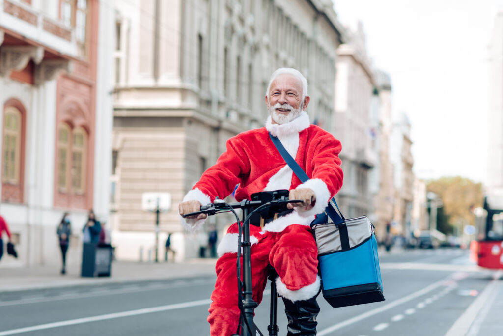 Man dressed like a Santa Claus cycling through the city and delivering orders