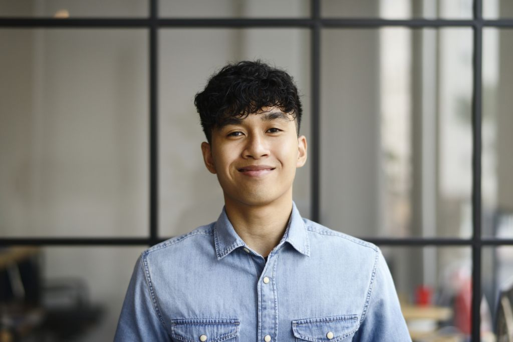 Portrait of a young Malay man in a modern office